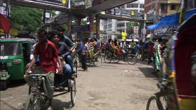 A running rickshaw with passengers aboard