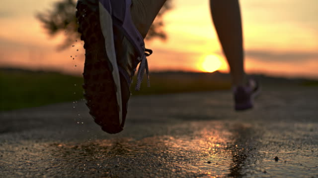 slo mo running shoe splashing on a wet asphalt - challenge stock videos & royalty-free footage