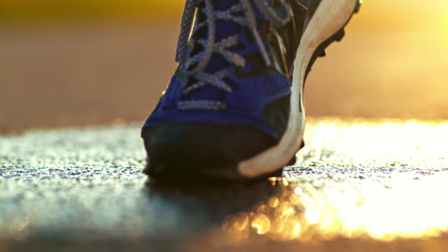 vídeos de stock e filmes b-roll de slo mo running shoe splashing on wet road - ténis calçado desportivo