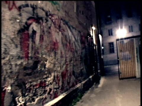 running through urban square of berlin back streets past graffiti covered walls into bright lights berlin - gasse stock-videos und b-roll-filmmaterial