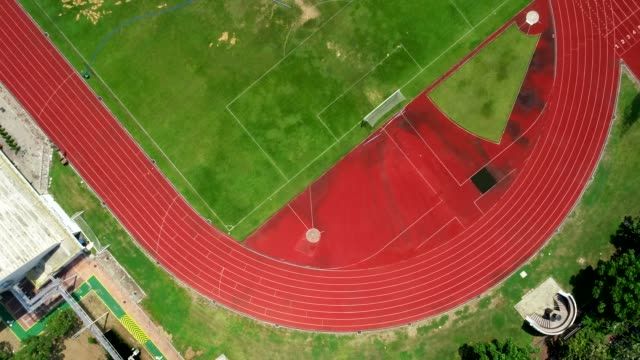 running track at the football stadium, color is orange brick, high angle view by drone. - running track stock videos & royalty-free footage