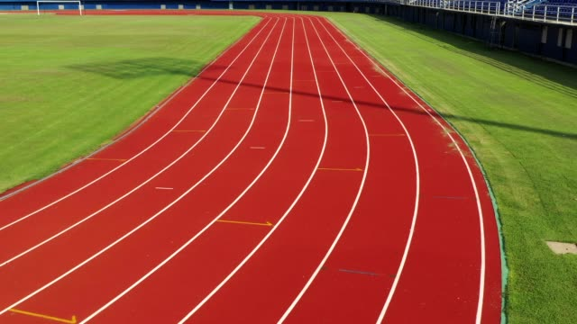 running track at the stadium, color is orange brick, high angle view by drone - pista di atletica leggera video stock e b–roll