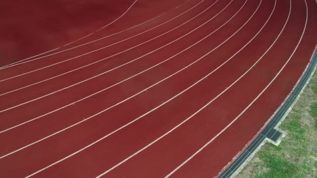 running track at the stadium, color is orange brick, high angle view by drone. - pista di atletica leggera video stock e b–roll