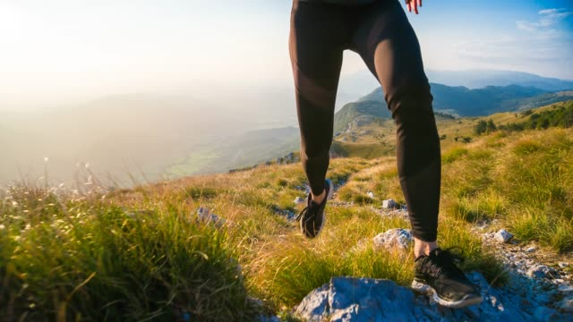 running uphill over rocky trails and grassy slopes in mountain terrain, green meadows in background - uphill stock videos & royalty-free footage