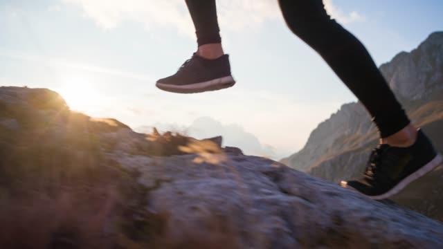 山岳地帯の岩だらけの小道と芝生の斜面で上り坂を走る - アウトドア点の映像素材/bロール