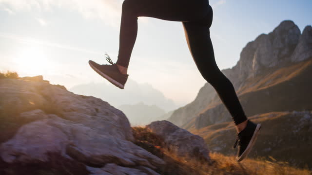 running uphill over rocky trails and grassy slopes in mountain terrain - uphill stock videos & royalty-free footage