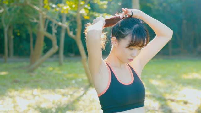 running women tying up hair before run - tie stock videos & royalty-free footage