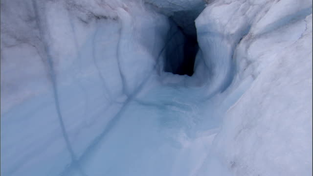 Runoff forms a tunnel near tents pitched on a glacier's surface. Available in HD.