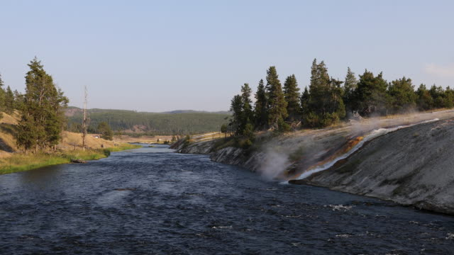 runoff from a hot spring flowing into the madison river. - mezzogiorno video stock e b–roll