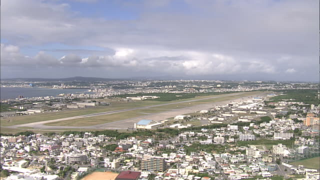 A runway of Marine Corps Air Station Futenma runs alongside the city of Ginowan, Japan.