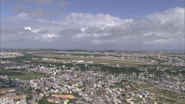 A runway of the Marine Corps Air Station Futenma runs alongside the cityscape of Ginowan, Okinawa.