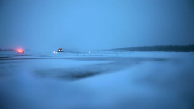 a runway/airstrip full of snow, a plow is scraping in a snowstorm evening - scraping stock videos and b-roll footage