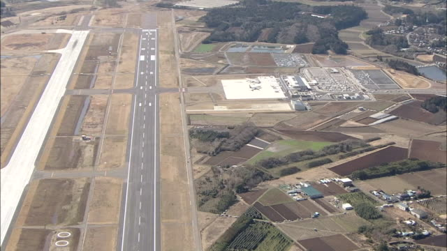 Runways extend past Ibaraki Airport into a rural area.