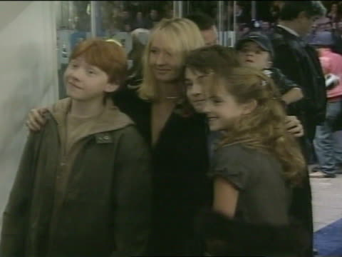 EVENING * Rupert Grint JK Rowling Daniel Radcliffe Emma Watson standing together in Odeon Theatre entrance posing for press photographs flashes...