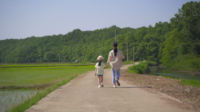 rural activity - mother and daughter strolling together - strohhut stock-videos und b-roll-filmmaterial