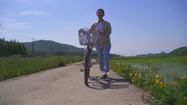 rural activity - young woman strolling with a bicycle by her side - ökotourismus stock-videos und b-roll-filmmaterial