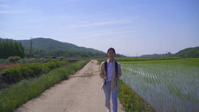 rural activity - young woman traveling with a backpack - ökotourismus stock-videos und b-roll-filmmaterial