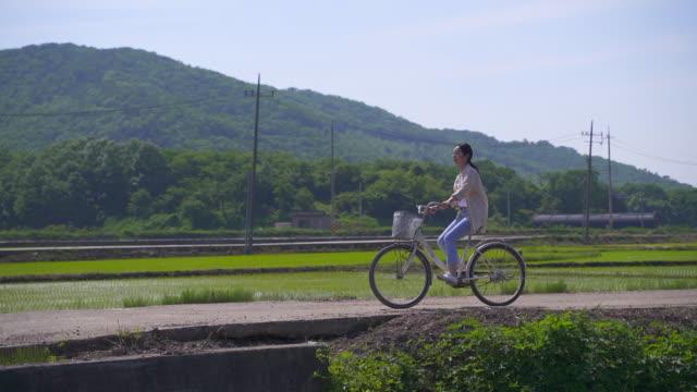 vídeos de stock e filmes b-roll de rural activity - young woman waving her hands while riding a bicycle - só mulheres jovens