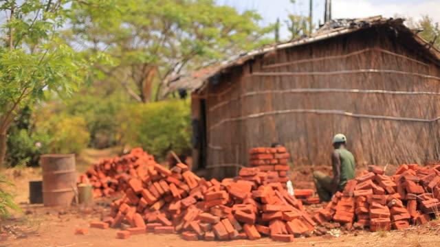 vidéos et rushes de constructeurs african rurales pose de briques pour construire la nouvelle maison - cabane structure bâtie