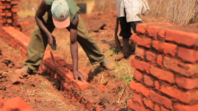 Rural African builders laying bricks to build new home