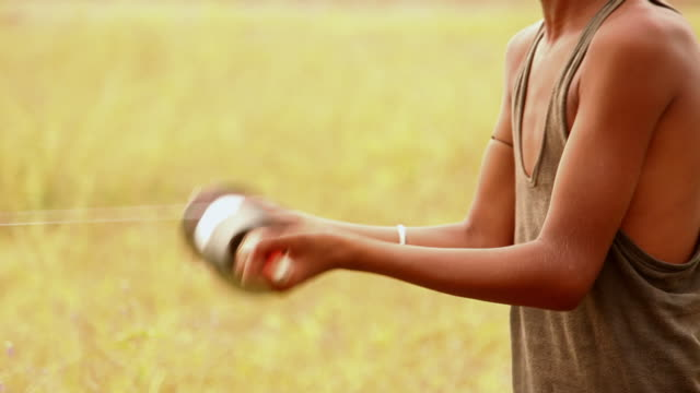 vidéos et rushes de rural boy rotating kite spool, haryana, india - corde