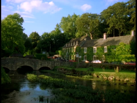 rural building, swan hotel, river coln and bridge, bibury - ducks on river, trees on skyline - perfection stock videos & royalty-free footage