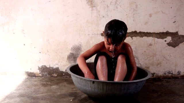 rural child bathing - povertà video stock e b–roll