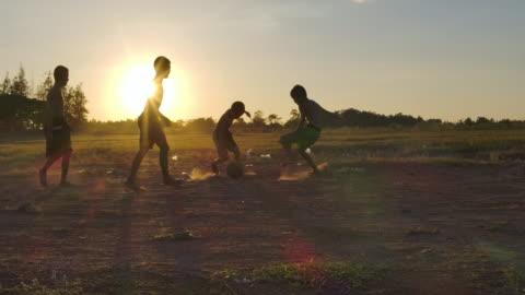 vídeos y material grabado en eventos de stock de los niños rurales están jugando al fútbol al atardecer.cámara lenta - cultura tailandesa