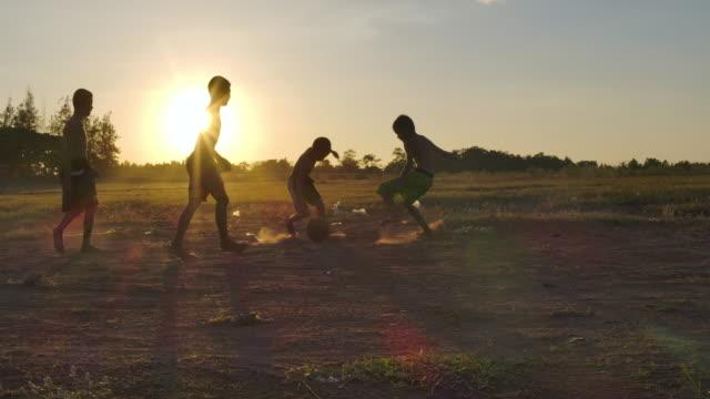 vídeos de stock e filmes b-roll de rural children are playing football at sunset time.slow motion - povo tailandês
