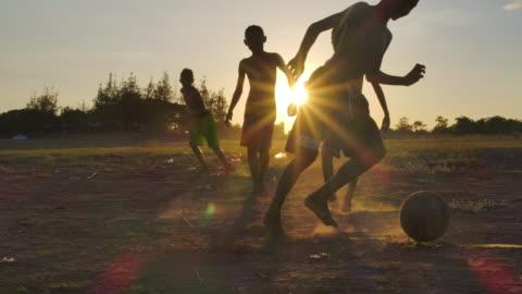 stockvideo's en b-roll-footage met bij zonsondergang spelen plattelandskinderen voetbal. slow motion - tegenspoed