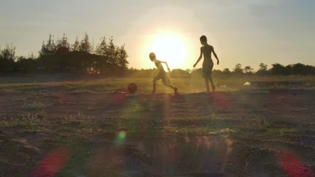 vídeos de stock, filmes e b-roll de crianças rurais estão jogando futebol no horário do pôr do sol.câmera lenta - termo esportivo