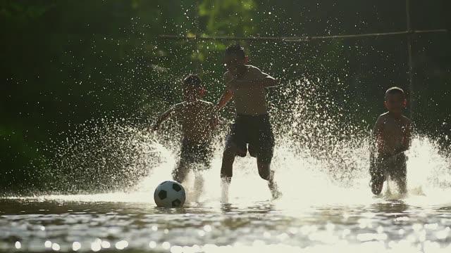 stockvideo's en b-roll-footage met landelijke kinderen spelen voetbal in de zon dag in een dorp. - arm lichaamsdeel