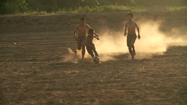 rural children are playing football in the sunshine day in a village. - poor family stock videos & royalty-free footage