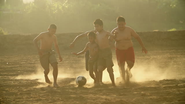 Rural children are playing football in the sunshine day in a village.