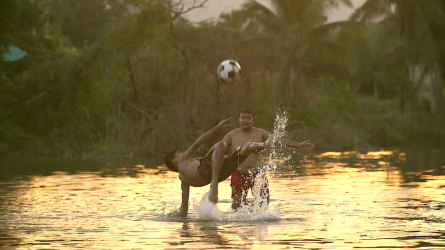 rural children are playing football in the sunshine day in a village. - small stock videos & royalty-free footage