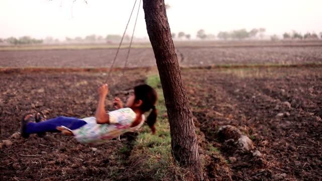 rural children swinging on rope - village stock videos & royalty-free footage