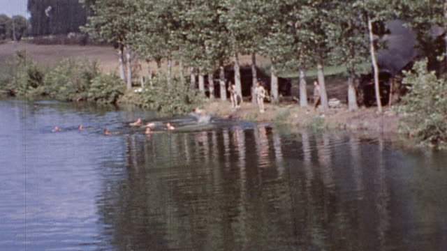 Rural countryside and US Army soldiers swimming nude in a lake splashing and waving / Normandy France