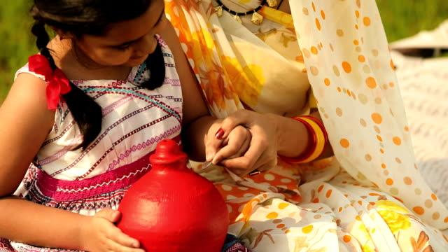 Rural family saving money into piggy bank, Haryana, India