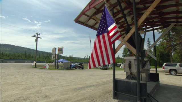 WS Rural gas station on side of highway with American flag blowing in foreground / Marion, Montana, USA