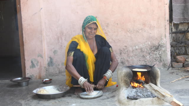 Rural Indian woman rolling dough