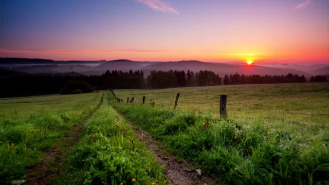 KRANICH BIS: Ländliche Landschaft mit Sonnenaufgang