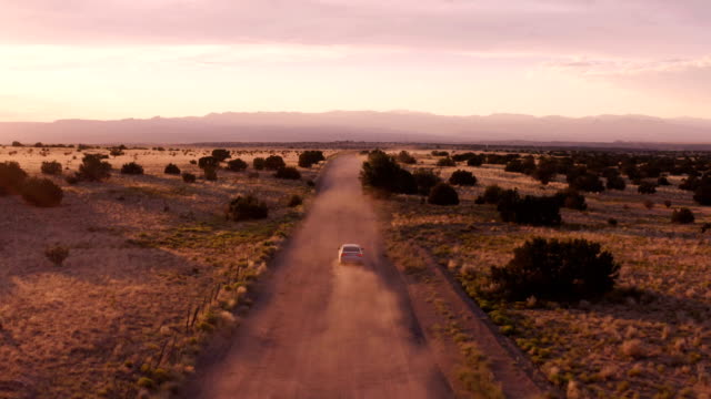 rural new mexico desert highway scene: car driving into the sunset on a dirt road - empty road stock videos & royalty-free footage