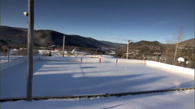 rural outdoor rink angled ws repeat pan repeat - アイススケート場点の映像素材/bロール