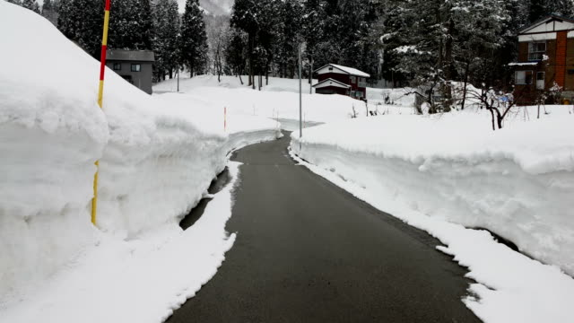 rural road carved through deep snow after a major winter storm hits northern japan - major road点の映像素材/bロール