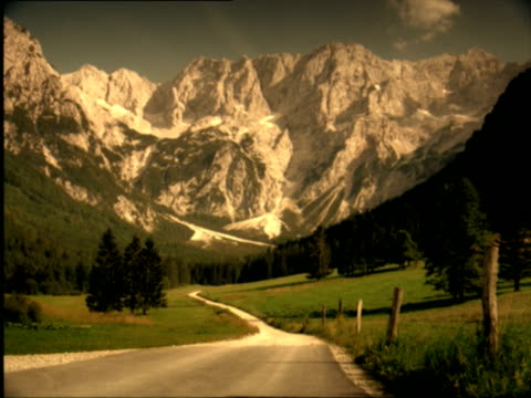 ws, rural road leading towards mountain range in distance, slovenia - placca di montaggio fissa video stock e b–roll