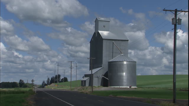 a rural road runs past a farm silo and grain elevator. - palouse stock videos & royalty-free footage