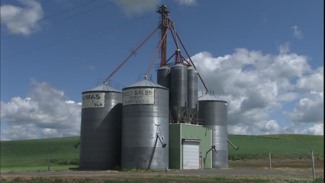 a rural road runs past farm silos and a grain elevator. - palouse stock videos & royalty-free footage