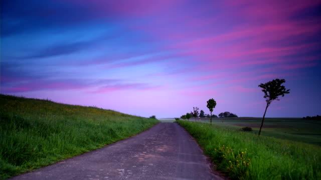 KRANICH BIS: Ländliche Straße bei Sonnenuntergang