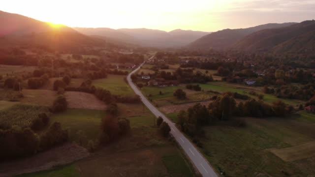 vidéos et rushes de une route rurale au coucher du soleil d'été doré - coucher de soleil dans les montagnes avec une vue sur les montagnes et le village - scènes apaisantes de la nature - village