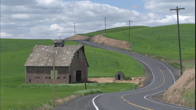 a rural road winds past a barn in the green countryside. - palouse stock videos & royalty-free footage